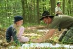 Elementary school project day in the national park Caption: A ranger and a girl are sitting on the forest floor