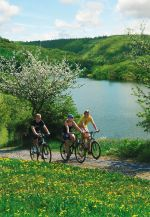 Through the national park by bike Caption: Three cyclists ride along the banks of the Edersee